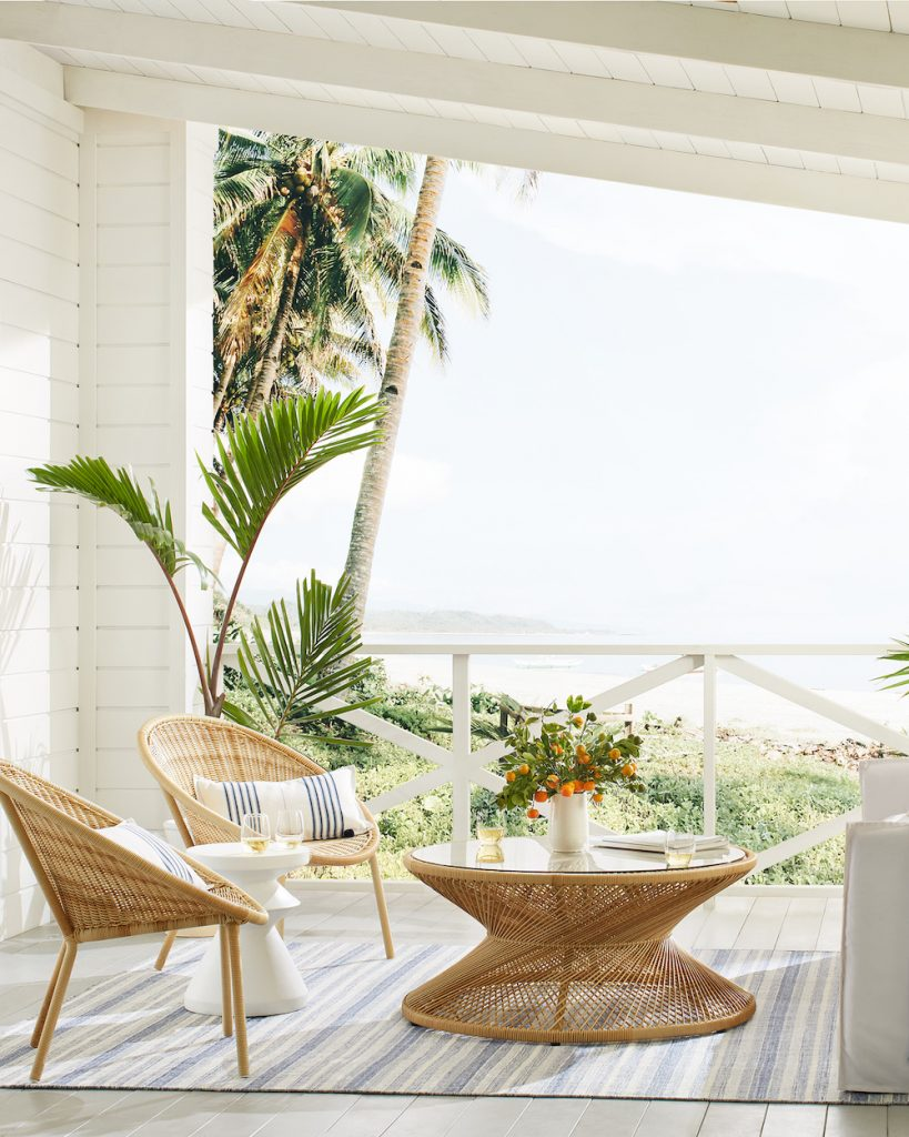 Elevate Your Outdoor Space Covered Deck Overlooking the Sea Rattan Chairs and Coffee Table by Serena and Lily #Coastal #CoastalDecorTips #BeachHouse #BeachHome #LakeHouse #CoastalDecor #SeasideDecor #IslandDecor #TropicalIslandDecor