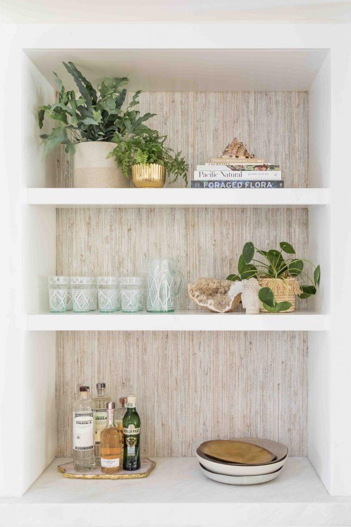 Coastal Bookshelf Decor Ideas Grasscloth Wallpaper #Coastal #CoastalDecor #Bookshelves #ShelfDecor #BeachHouse #BeachHome #LakeHouse #CoastalDecor #SeasideDecor #IslandDecor #TropicalIslandDecor